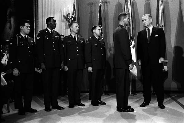 Standing on platform (L-R:) Spc-4 Gary Wetzel, Spc-5 Dwight H. Johnson, Sgt. Sammy Davis, Capt. James Taylor, Capt. Angelo Liteky, and President Lyndon B. Johnson.  Source:  LBJ Library photo by Yoichi R. Okamoto.