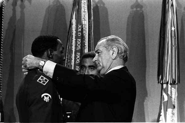 President Lyndon B. Johnson puts the Medal of Honor on Spc-5 Dwight Johnson as Col. James Robinson (center) looks on.  Source:  LBJ Library photo by Yoichi R. Okamoto.
